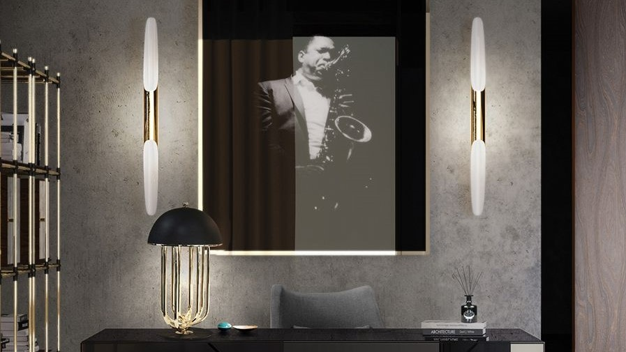 The Turner lamp by Delightfull can be seen in an office. The lamp has a black matt lamp head and gold accents on the legs.