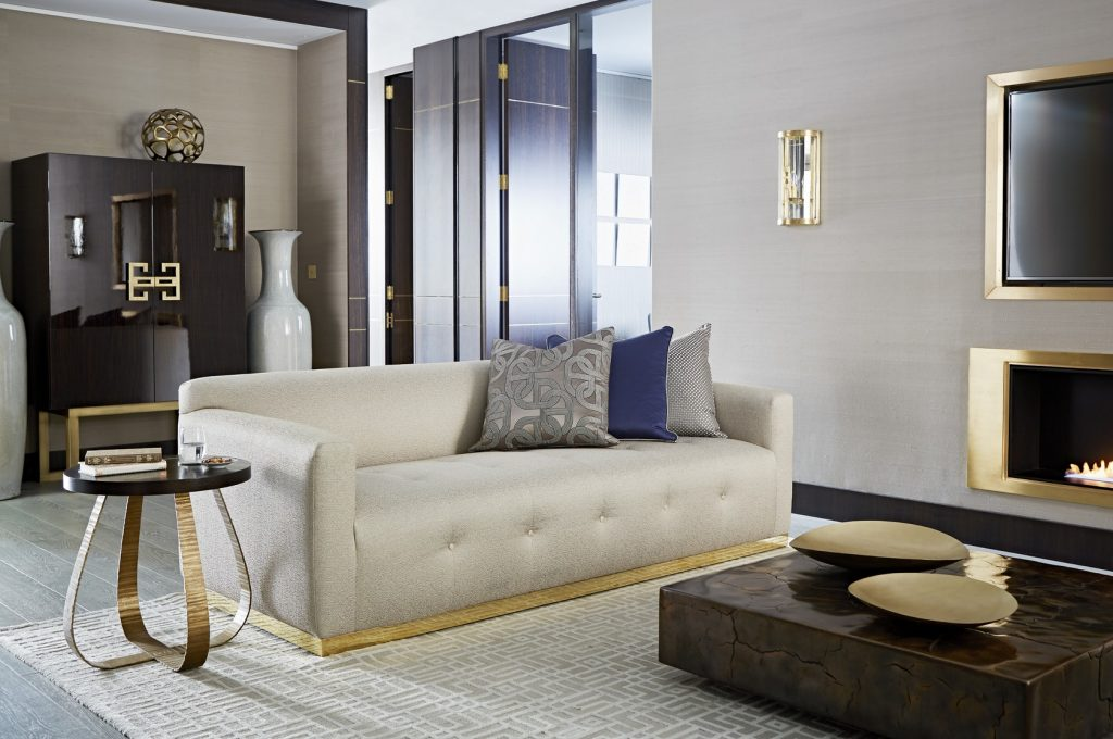 A neutral colored living room with an Art Deco side table.