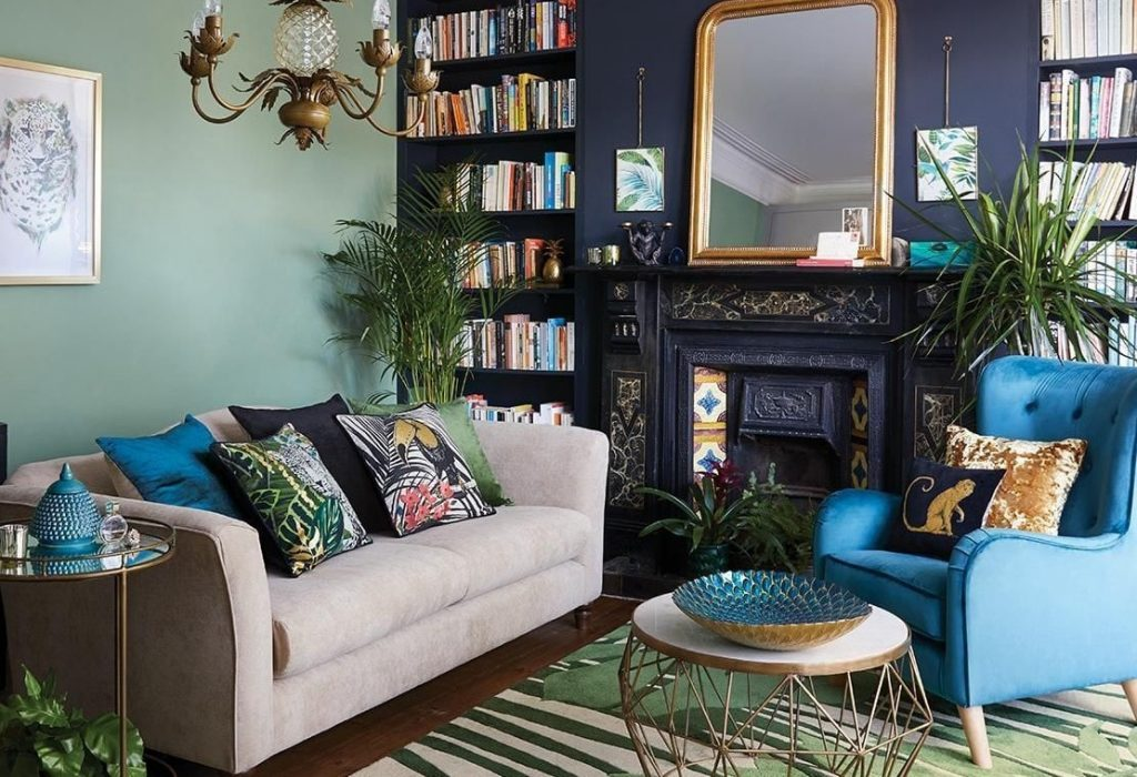 An eclectic living room with golden brass accents on furniture pieces from different styles and a mix match of colors on cushions, small details, etc.