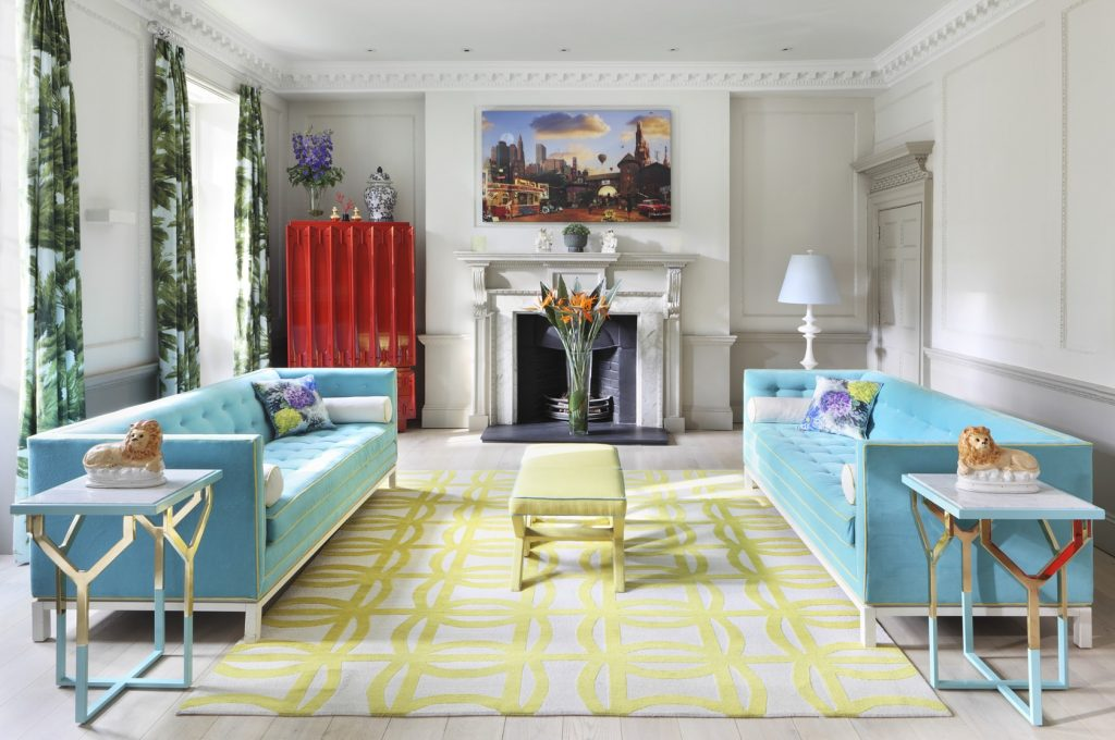 A white living room with bold accent colors. Baby blue sofa's, a bright yellow rug and coffee table and a bold red cabinet.