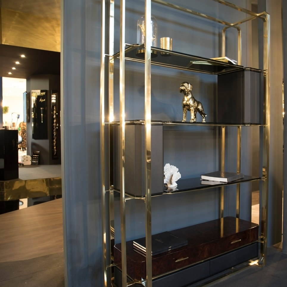 The Waltz bookcase by Luxxu is an elegant bookcase in gold and metal with brown drawers.
