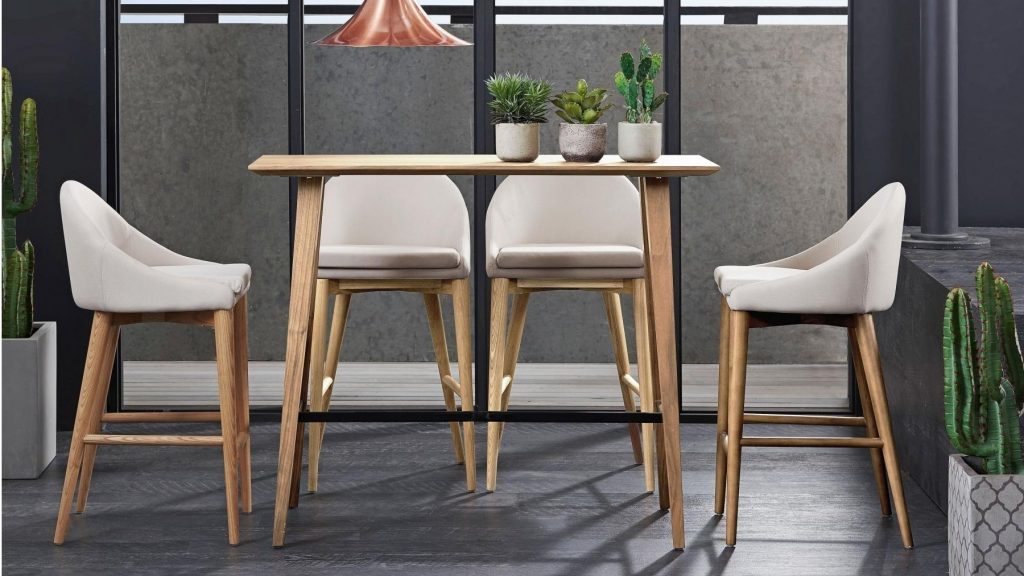 A light wooden dining table with 4 chairs with the same light wooden legs and white cushions.