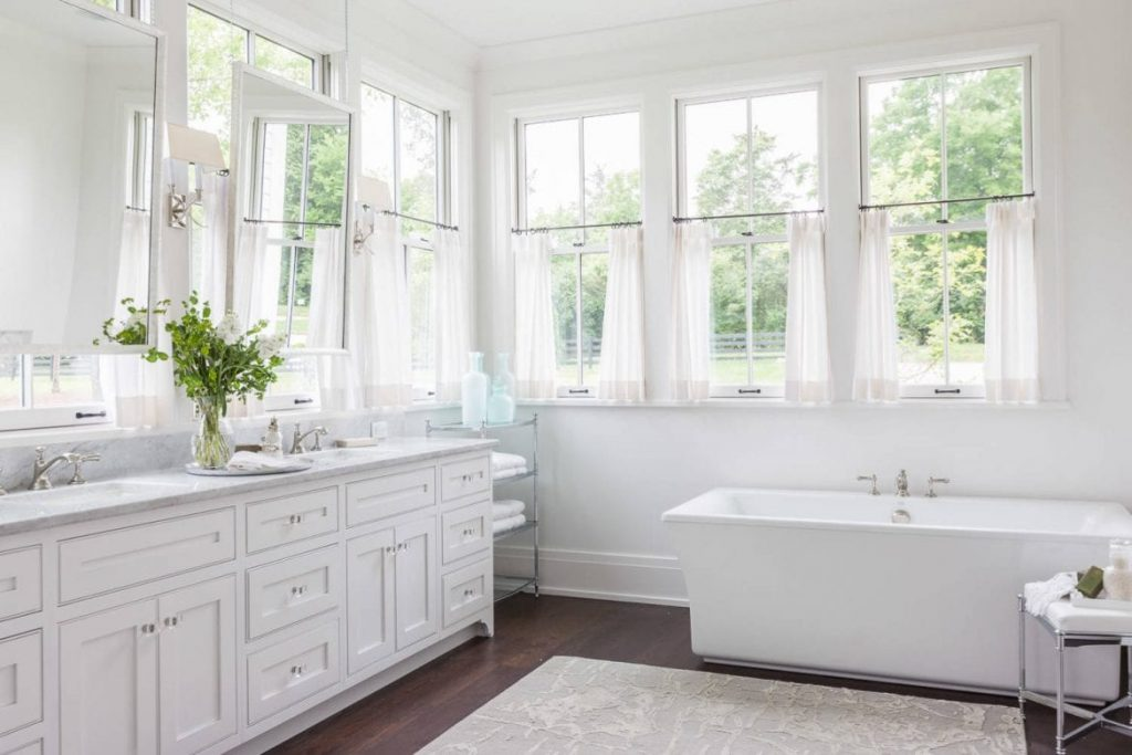 A white bathroom with multiple windows, also in front of the vanities.