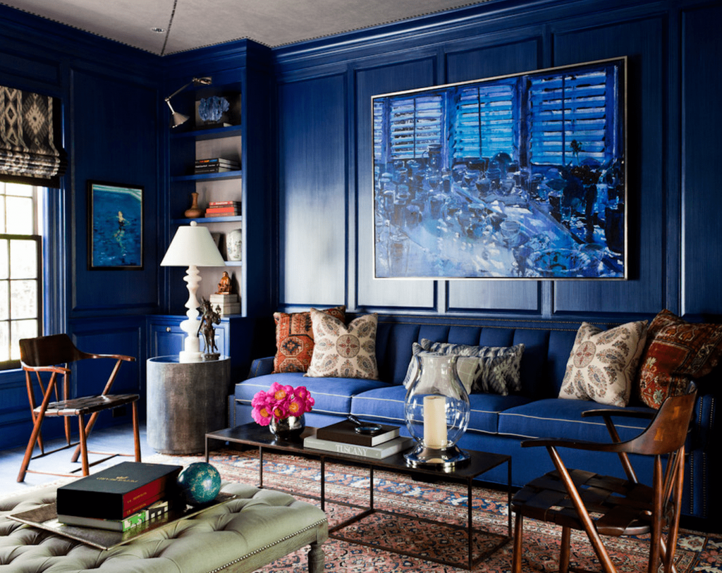 A navy colored living room with furniture that gives a boho vibe