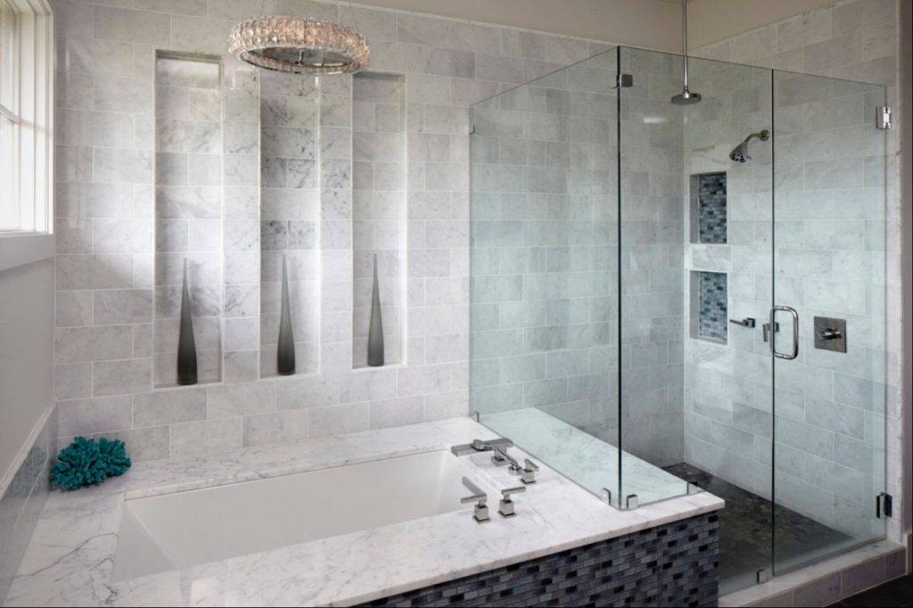 A grey and white marble bathroom with a bathtub and large shower.