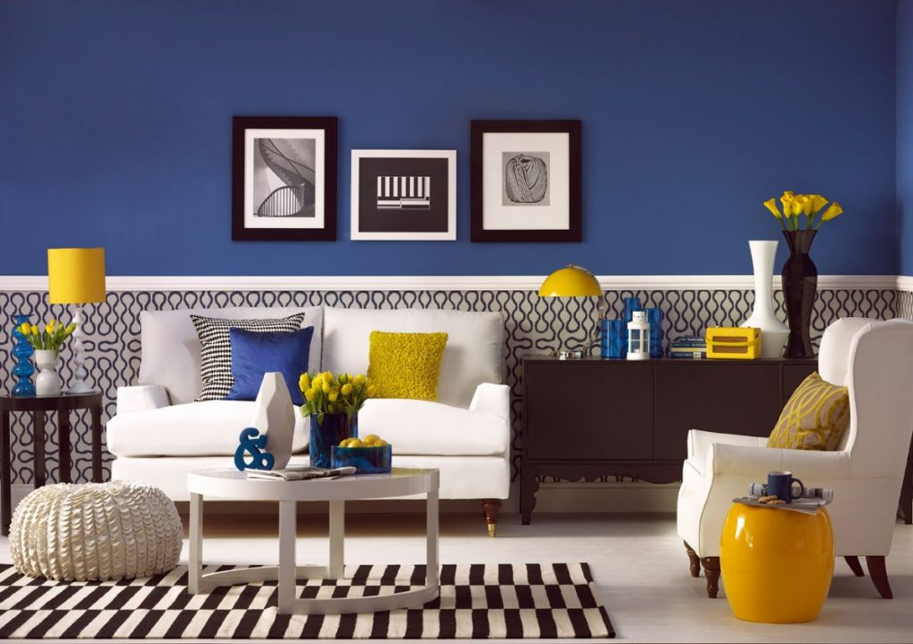 Navy colored living room with bold yellow and white accents.