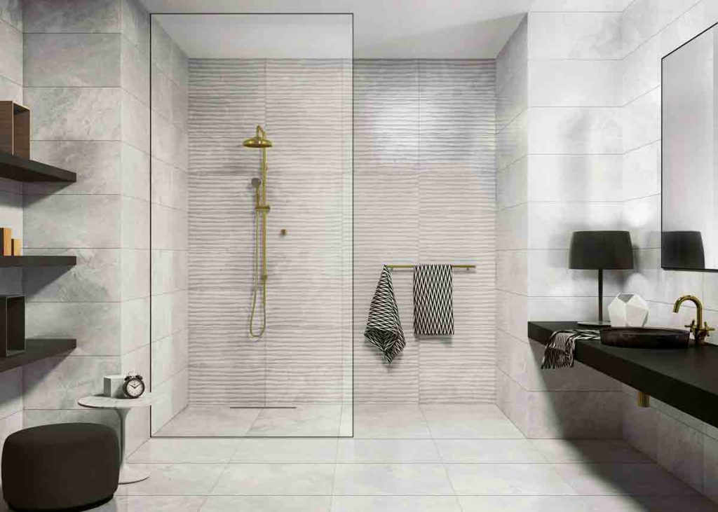A white marble bathroom with a shower and black vanity and shelves.