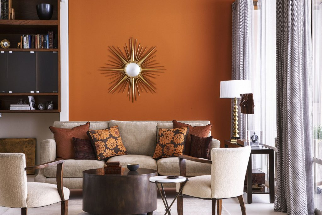 A bold orange living room with grey and white accents.