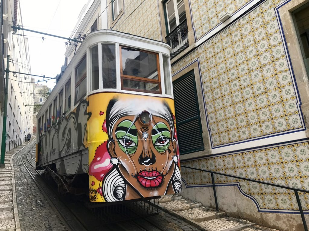 A tram in Lisbon with grafitti of a female face on the back.