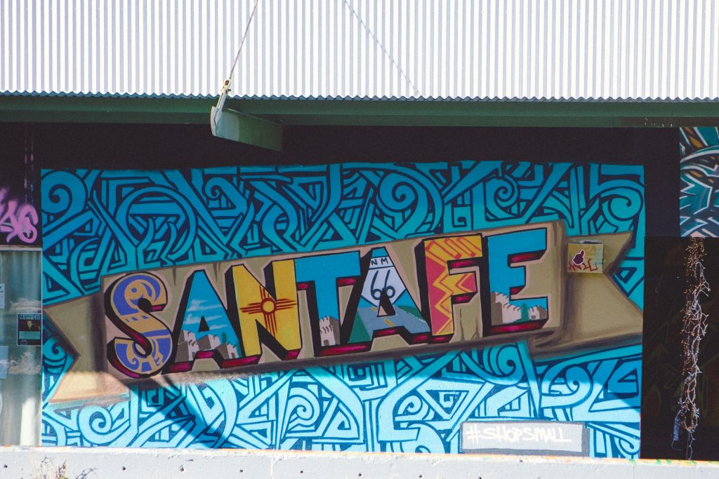 A wall with graffiti showing the name of the city and elements that are part of their culture.