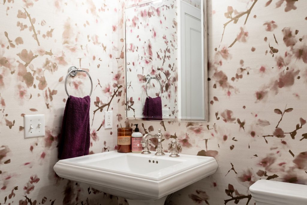 Bathroom trends with illusion are created in this powder room with the use of a pink flower wallpaper.