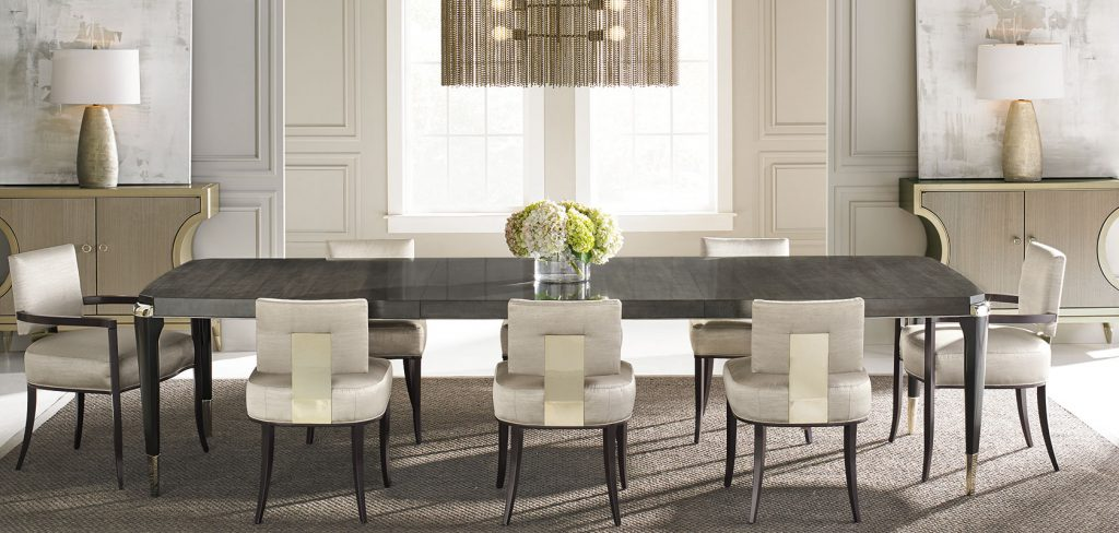 A grey dining rable with black legs and metallic finishes with white cushion chairs with black legs.