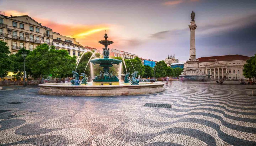 A square in Lisbon with a fountain and a big memorial statue in the back.