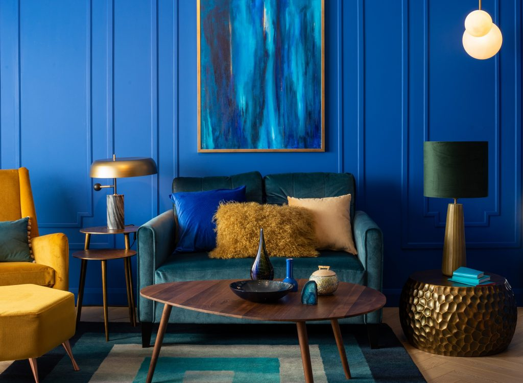 Dark blue living room walls with a velvet blue and yellow sofa in front of the wall.