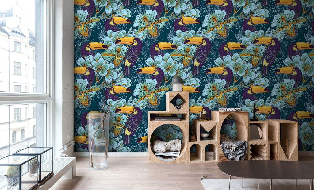 A room with dark green wallpaper with purple pelicans and light blue flowers.