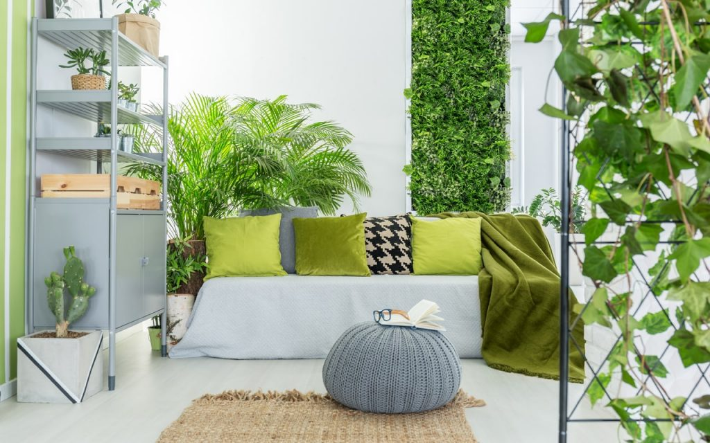 Biophilia in interior design. Small reading corner with plants and a jute rug.