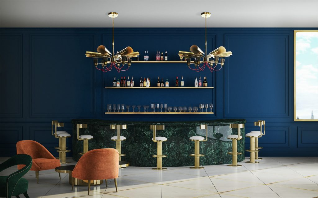 A navy colored bar of a hotel with gold accents throughout the room.