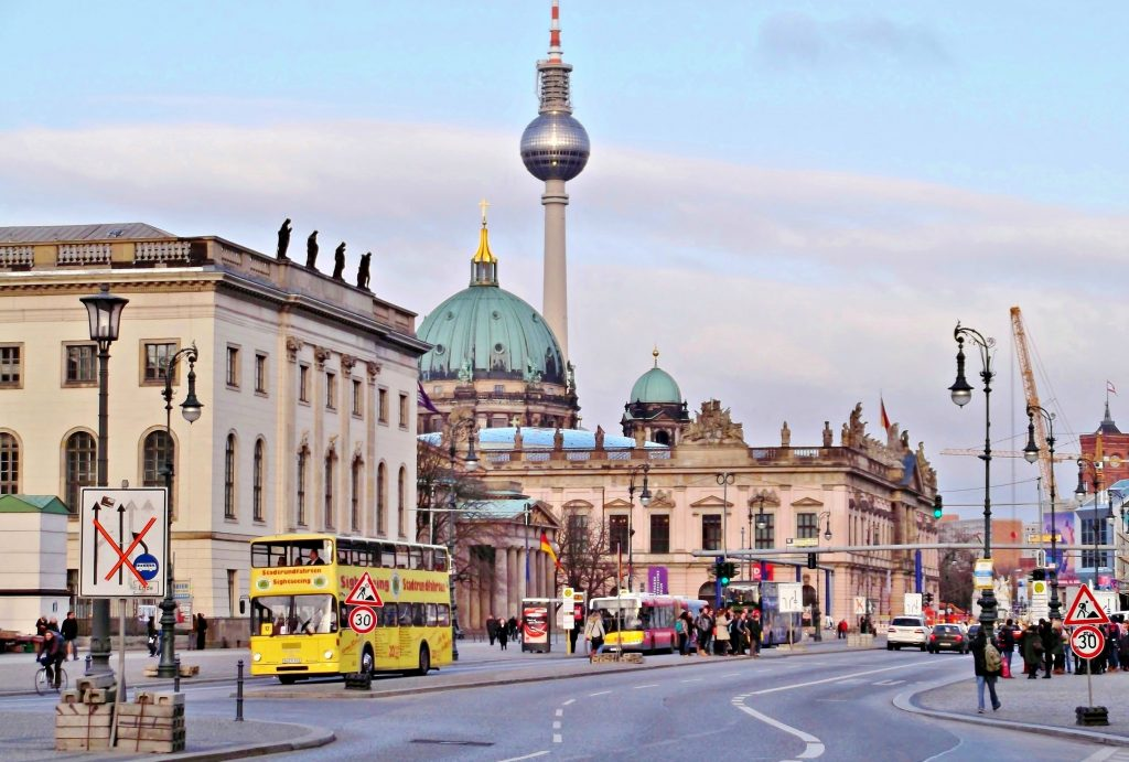 A busy street in Berlin with historical buildings and the Fernsehturm in the background.