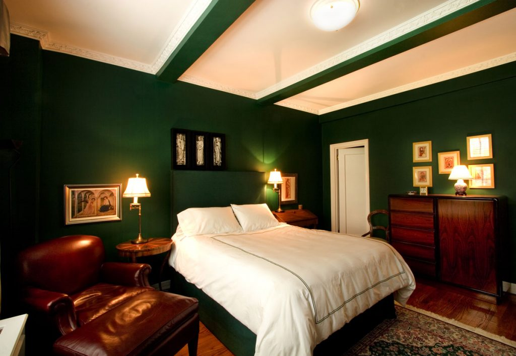 Dark green bedroom with dark brown furniture