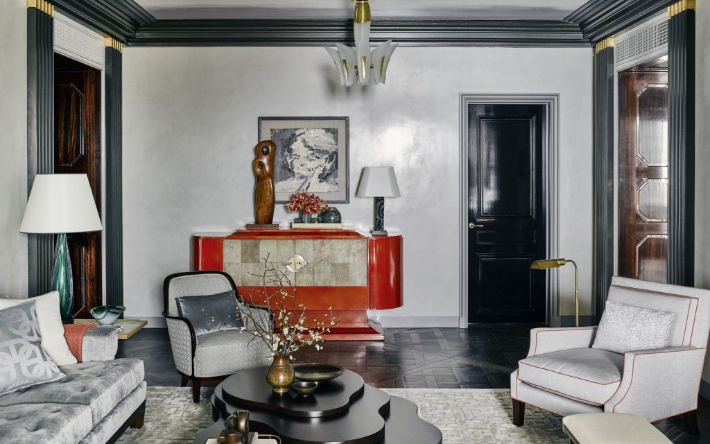A grey living room with a bold red cabinet and a uniquely formed coffeetable.