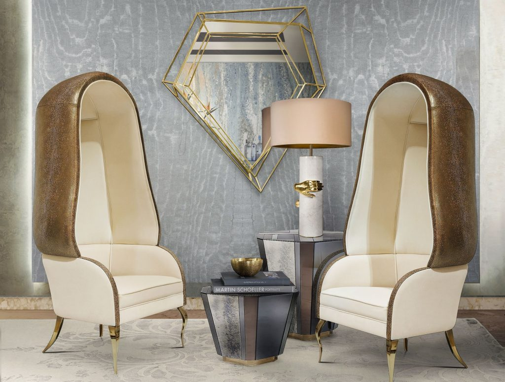 This seating area has 2 Drapesse chairs by Koket. The Drapesse chair has white seating cushions but a dark brown leather cover and gold legs.