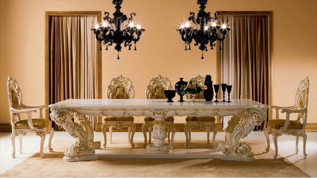 A white and gold dining rable and dining chairs in a very classical and detailed style.