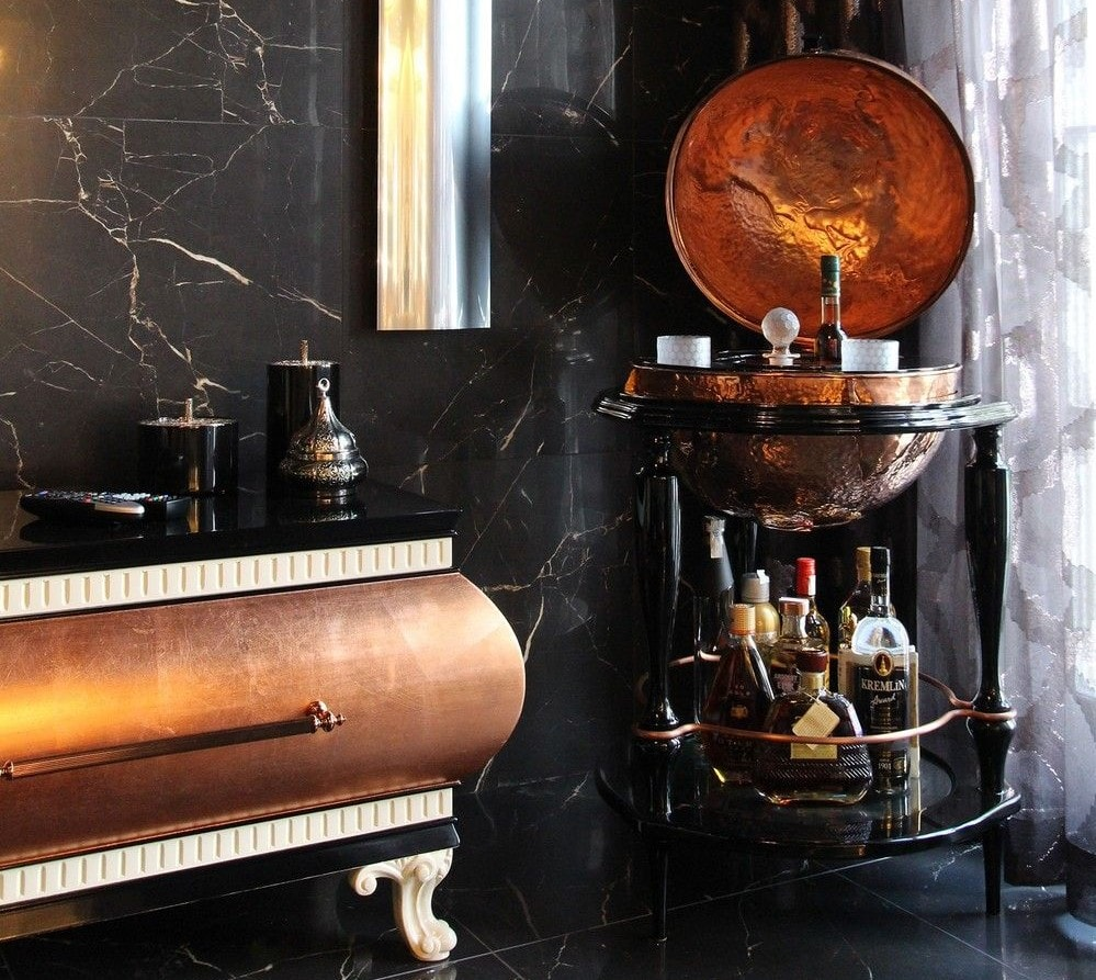In the corner of a room we have the Equator Glob bar by Boca do Lobo. This bronze globe sits in a black wooden installation with 3 legs. The globe houses glasses and alcoholic bottles. Underneath the globe between the legs is also space for more bottles.