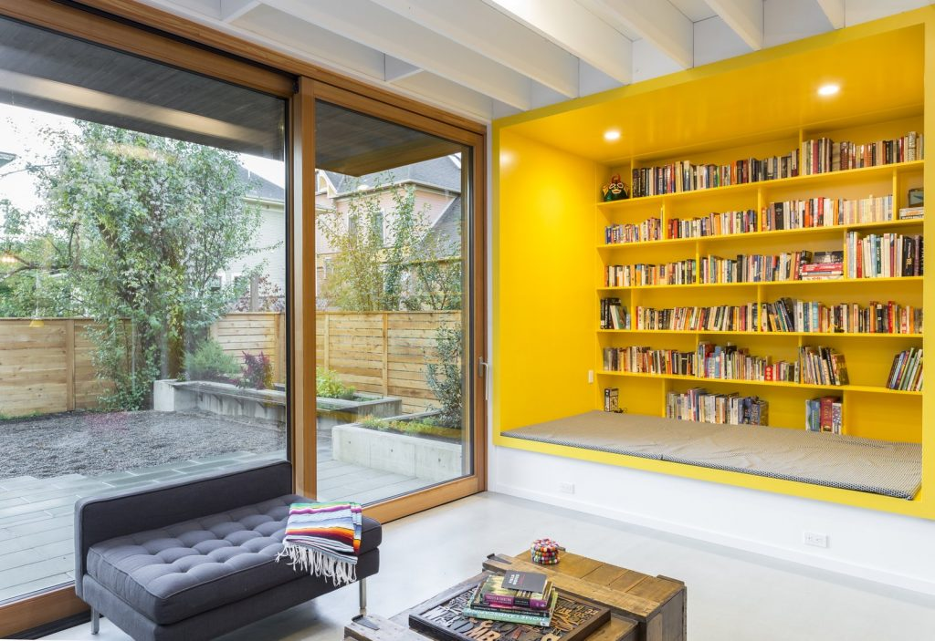 Bold Yellow reading corner in a living room that looks out on a garden.
