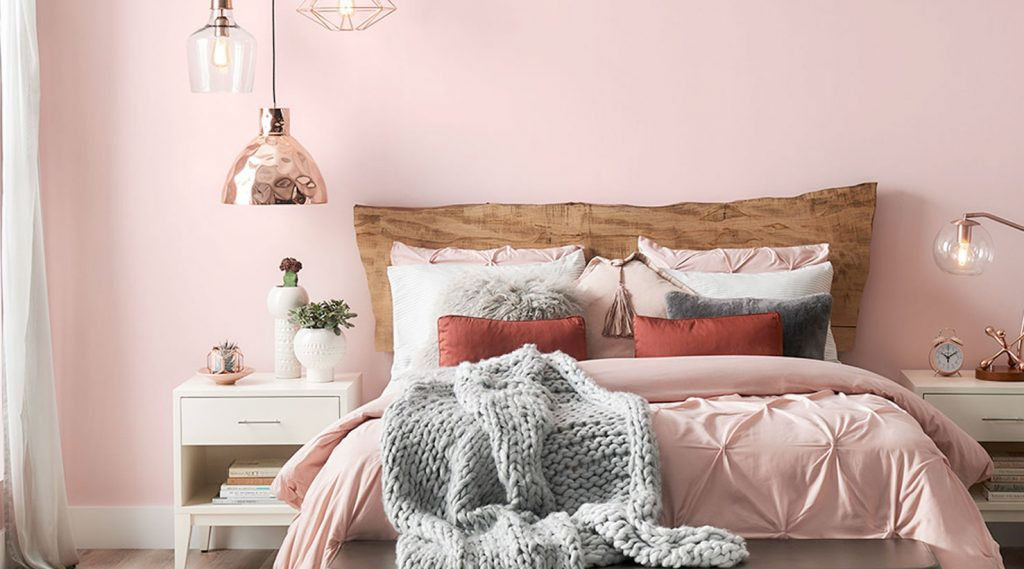 A pale pink bedroom with grey, white and metallic accents.