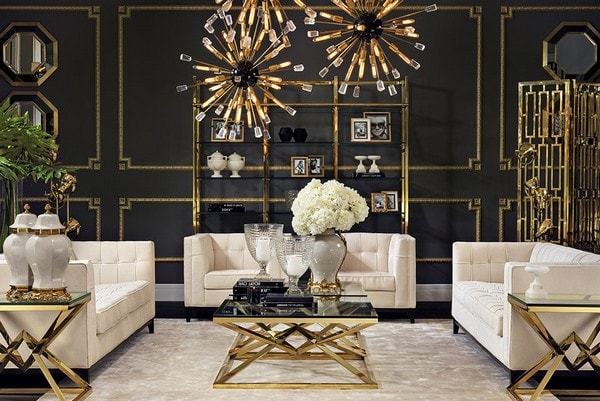 A symmetric living room with golden accents on the lamps, coffee table, side tables, etc. and white sofa's.