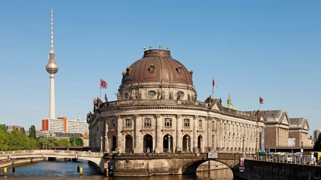 A view of a museum in Berlin by the Spree river with the fernsehturm in the background.
