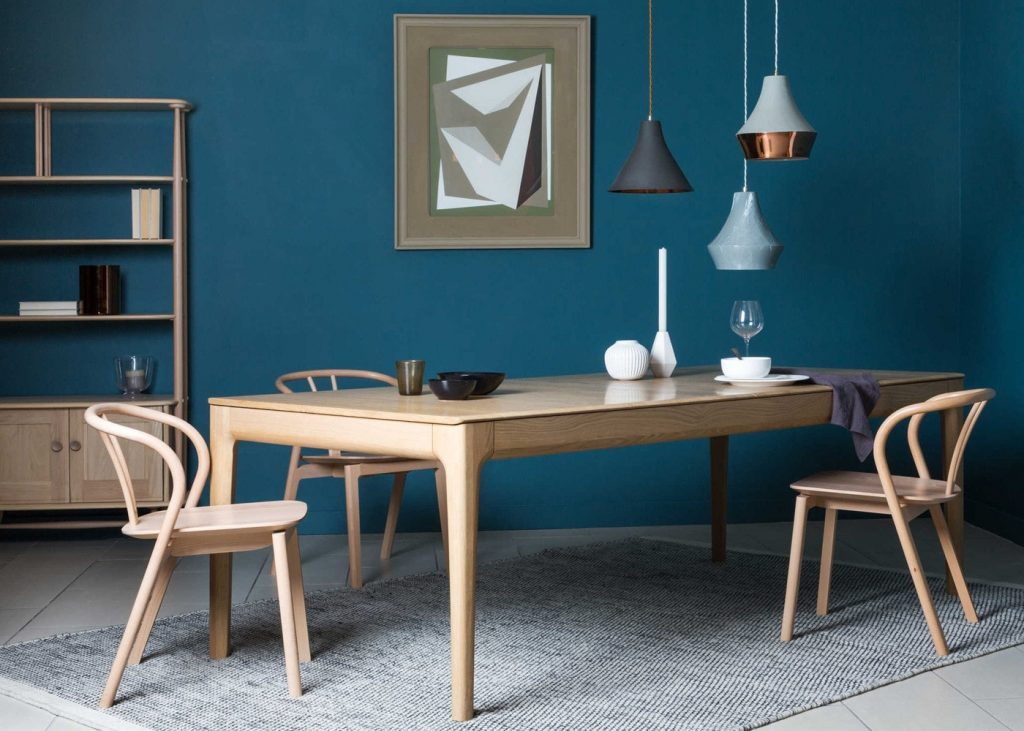 A light wooden dining table with corresponding chairs.