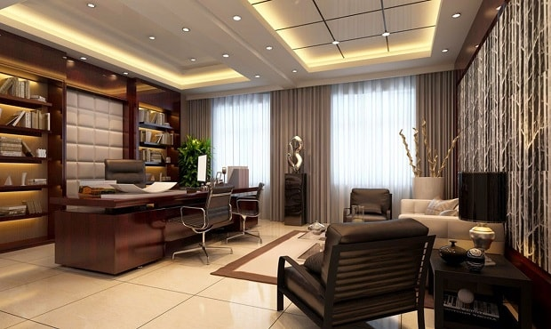 Luxury office with grey leather seats, and dark wooden desk and bookcase.