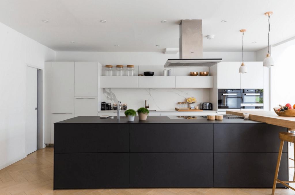 A white kitchen with a black kitchen island.