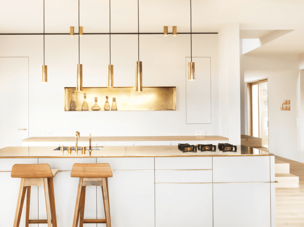 A white kitchen with brown and gold accents.