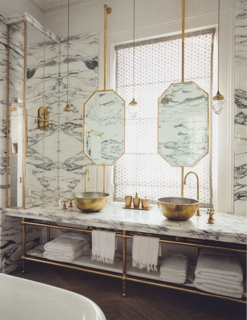 White marble table, the brass suspension lamps and the wooden flooring bathroom