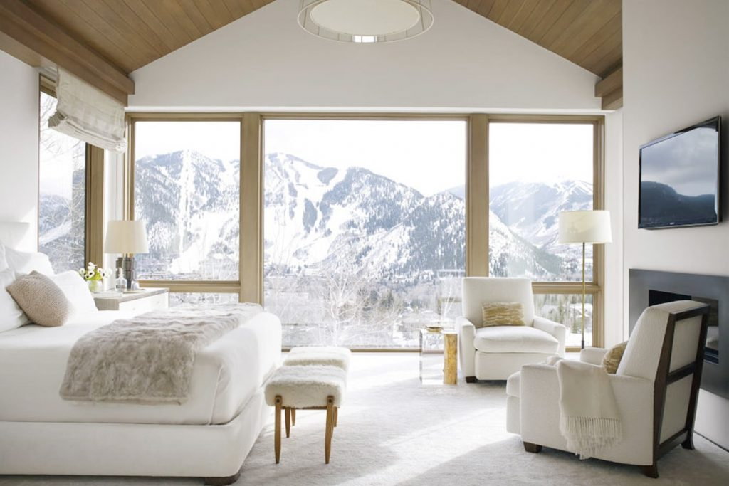A white and brown bedroom with a fantastic mountain view is one of the amazing designs by American interior designer, Victoria Hagan.